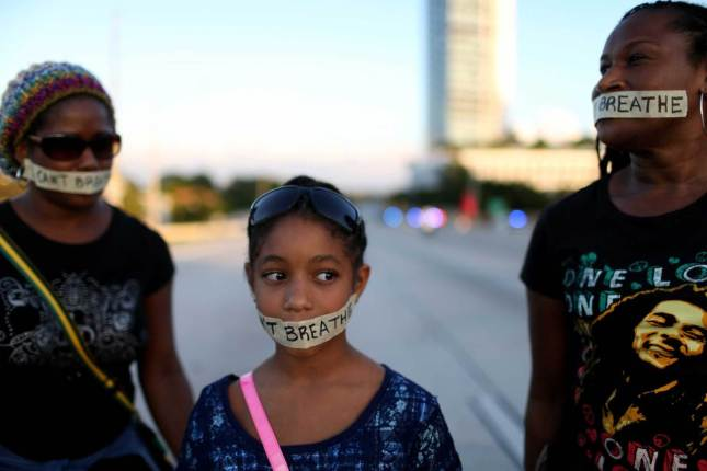 "Demonstrators stand with tape reading, "" I Can't Breathe"", as they march along Interstate 195 after police shut the road down on Dec. 7, 2014 in Miami. Joe Raedle—Getty Images"