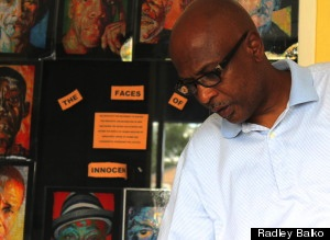 John Thompson, in front of a gallery of other exonerees.